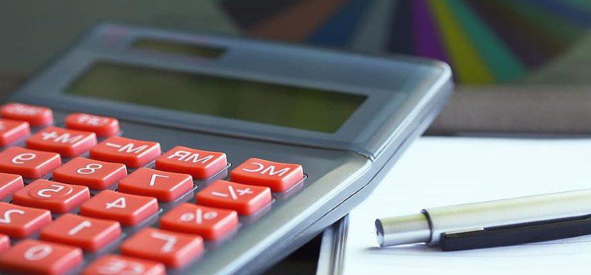 kalkulator, kartka papieru i długopis na biurku