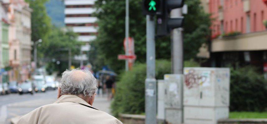 starszy mężczyzna przechodzący przez jezdnię