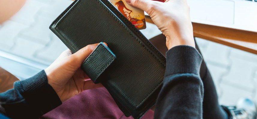 osoba sięgająca do portfela po kartę kredytową
